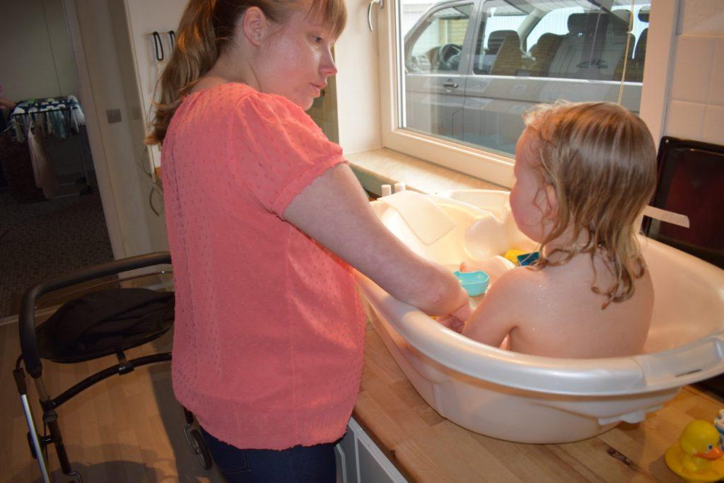 Billede af mor, der bader sit barn på køkkenbordet